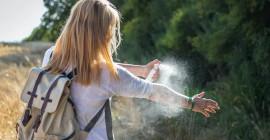 женщина распыляет средство от насекомых